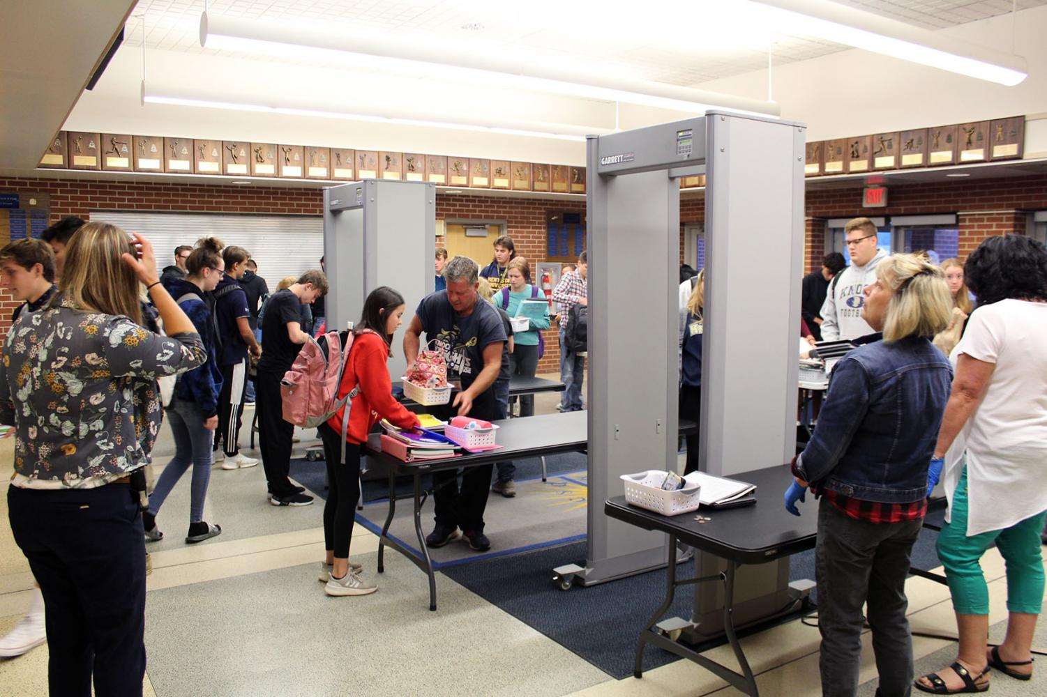 Students try not to drop their things as they shuffle through the newest technological advancement of KHS: metal detectors.