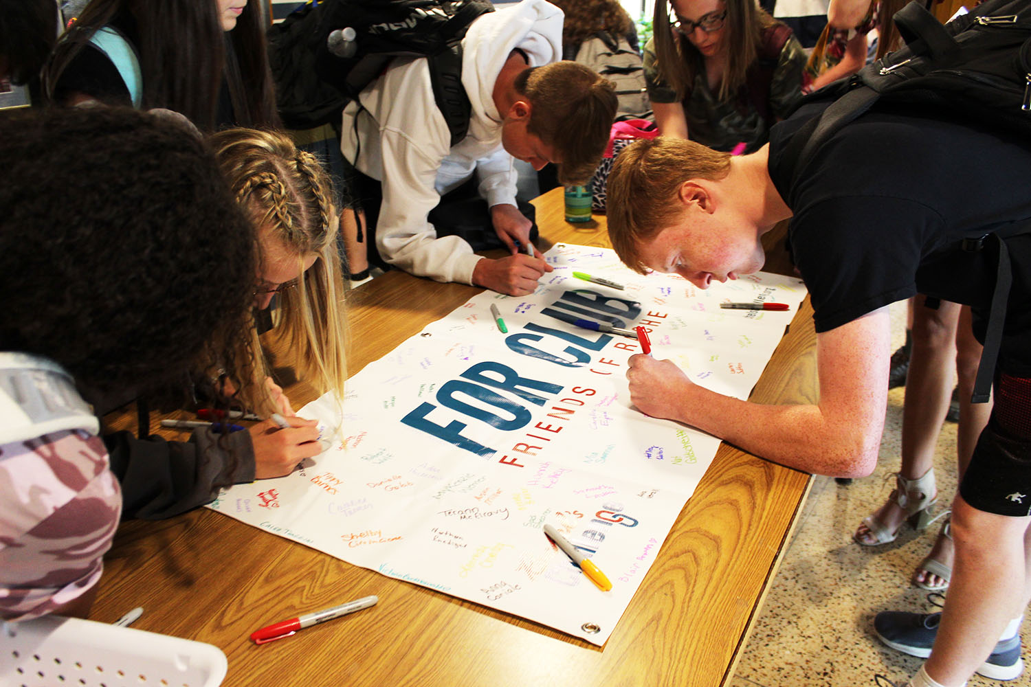 Students sign the FOR club banner, showing they will take the challenge. Over 100 students have joined.