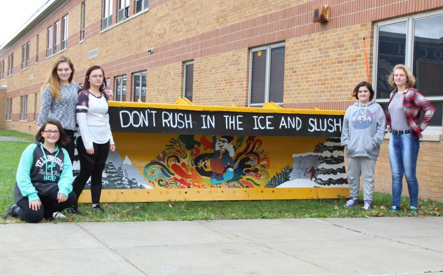 Some of Mr. Kamer's art students pose beside their art project - a painted snow plow.