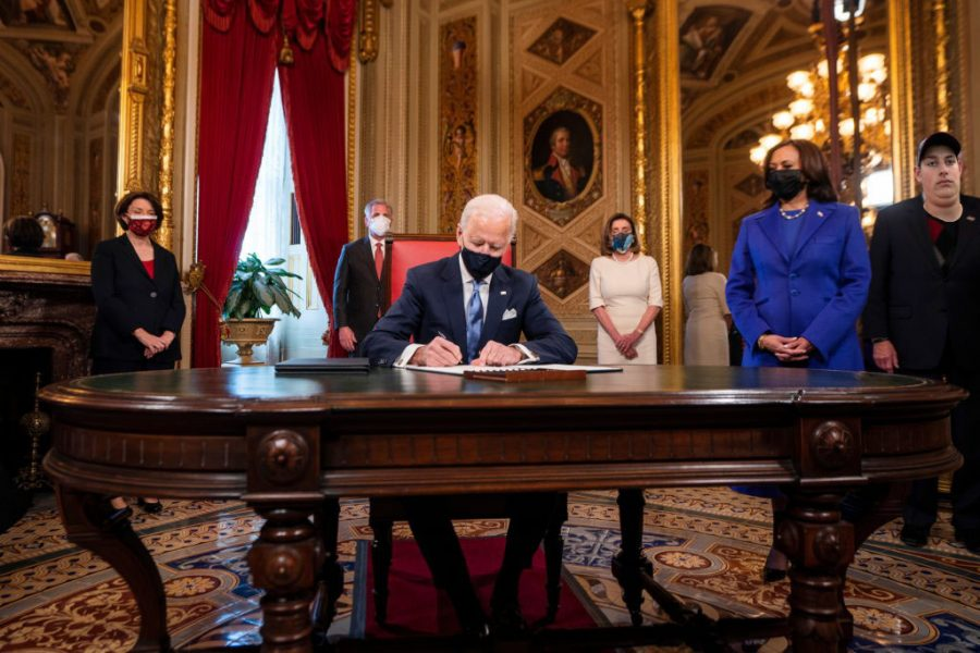 U.S. President Joe Biden signs three documents including an Inauguration declaration, cabinet nominations and sub-cabinet nominations, as U.S. Vice President Kamala Harris watches in the Presidents Room at the U.S. Capitol after the 59th Presidential Inauguration in Washington, U.S., January 20, 2021. Jim Lo Scalzo/Pool via REUTERS